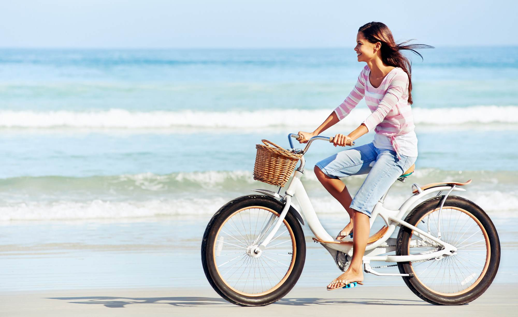 Girl on bike riding on sea shore