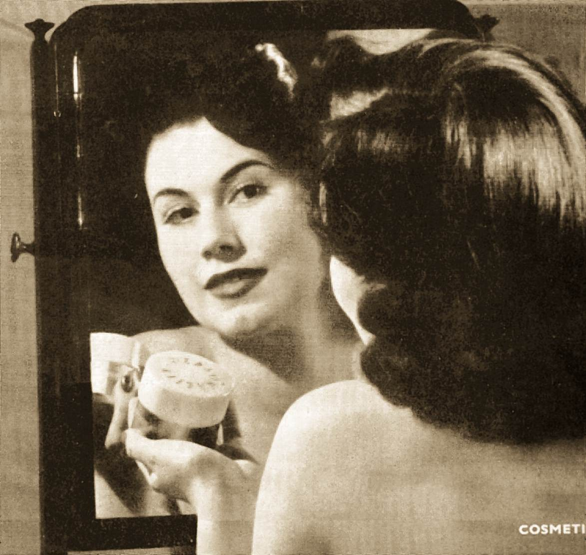 woman putting on cosmetics